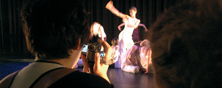 Lady videoing student performing a dance routine.