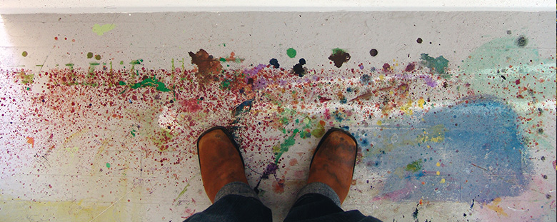 Looking down a shoed feet standing ontop of a floor splattered with paint